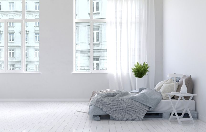 3D rendering of unmade bed with gray blankets in sparsely decorated bedroom interior with hardwood floor