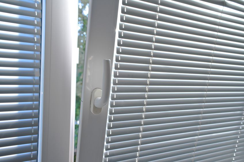Venetian blinds on window, close up image focusing on window handle.